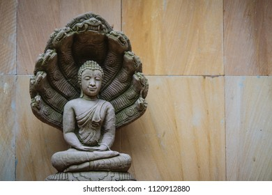 Beautiful Buddha statue made of sand stone and cover with Naga heads. Stone Buddha statue with seven Phaya Naga heads. Outdoor stone seated Buddha image protected by 7 heads Naga spreads cover on top.