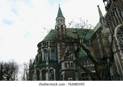 Beautiful building with a big windows. Catholic Church. Neo-Gothic style. Building with a green roof and blue windows. On the blue sky background.