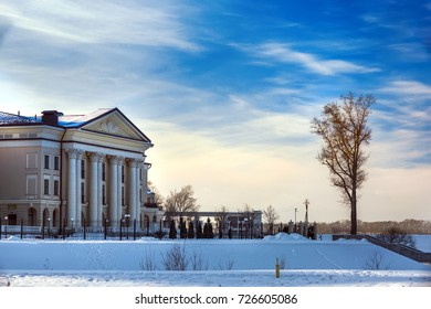 A beautiful building with columns on the banks of the Volga River next to the trees.