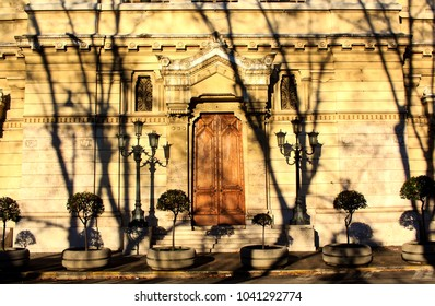 Beautiful building facade in Rome, Italy. Building is lighted-up by the evening sun with deep trees shadows on it.