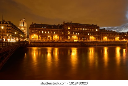 Beautiful building of hospital 'Hotel Dieu' at 'Ile de la Cite' in Paris. Reflection of warm street lamps in Seine river.Famous 'Notre Dame' church in background.