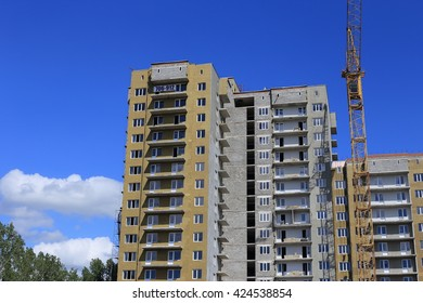 beautiful building and a successful business  build tall buildings for residents. standing next to a construction crane. blue sky