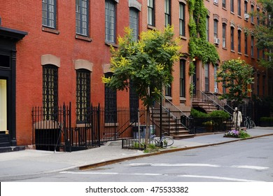 Beautiful buildings in Greenwich Village, Soho district. Entrance doors with stairs and trees, Manhattan New York. Classic red brick apartment building in New York City. Beautiful american street.
