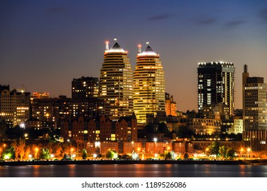 Beautiful buildings, skyscrapers and towers of the Dnepr city are reflected in the Dnieper River at night, Ukraine.   Dnipro, Dnepropetrovsk, Dnipropetrovsk