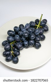 A beautiful bunch of dark blue grapes on a white plate. Minimalistic food photography.