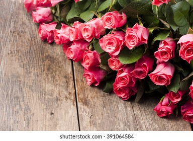 Beautiful bunch of roses on wooden background.