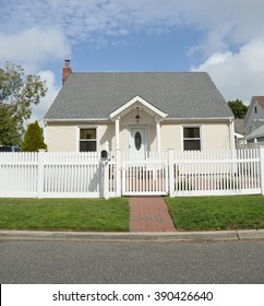 Beautiful Bungalow Home with white picket fence sunny blue sky clouds day residential neighborhood USA
