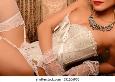 Beautiful burlesque girl in white corset lying on the sofa, studio shot.