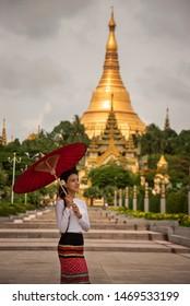 Beautiful Burmese girls wearing national costumes Apply Tanaka powder on the cheeks, and the view of, Shwedagon Pagoda, Myanmar