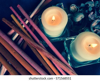 Beautiful burning candles and aromatic sticks on a black background wallpaper