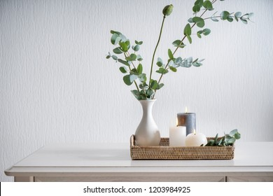 Beautiful burning candles with green leaves in vase on white table