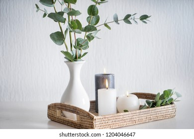 Beautiful burning candles with green leaves in vase on wicker tray