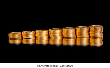 beautiful business chart concept of golden coins, shows an slow increase is isolated on black background