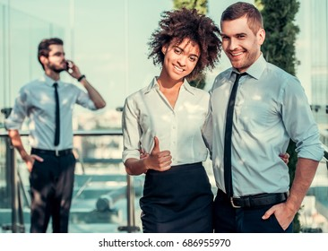 Beautiful business couple is looking at camera and smiling while standing on balcony of the office building, businessman in the background