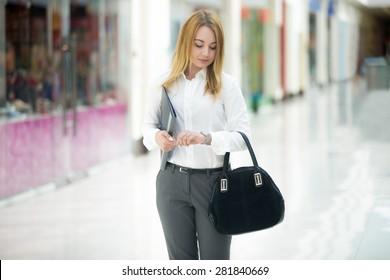 Beautiful business girl wearing office style outfit holding document dossier and suede bag, looking at wristwatch, checking time, running late or waiting