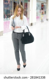 Beautiful business girl wearing smart casual style clothes holding folder with documents and handbag, looking at watch, checking time, walking in a hurry