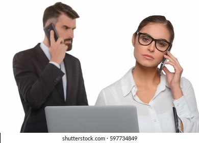 Beautiful business lady in focus. Young manager woman holding an opened notebook in one hand and a phone in other hand, while her boss has an important call.