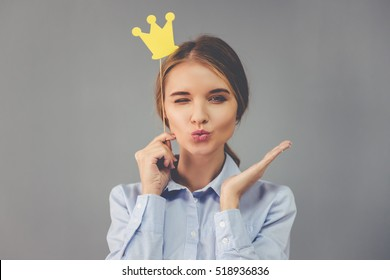 Beautiful business lady is holding party crown on stick, looking at camera and sending air kiss, on gray background
