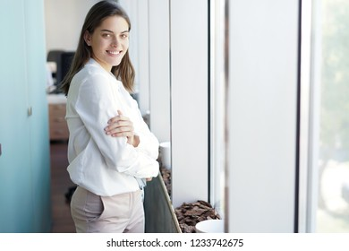 Beautiful business lady is looking at camera and smiling while working in office.
