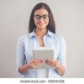 Beautiful business lady in smart casual wear and eyeglasses is using a digital tablet and smiling, on a gray background