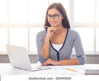 Beautiful business lady in smart casual wear and eyeglasses is holding a pencil, looking at camera and smiling while sitting at the desk in office