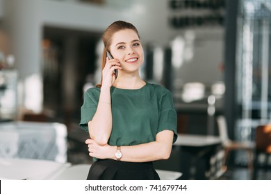beautiful business lady at work with a laptop and phone sitting in the office