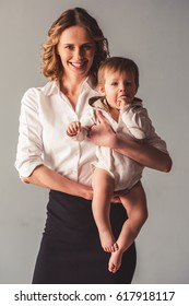 Beautiful business mom in suit is holding her cute baby boy, looking at camera and smiling, on gray background