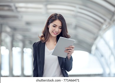 Beautiful business people 20-30 years old hand holding smartphone are reading online news through tablet on go to work in the morning. articles news and travel on the website online.technology concept