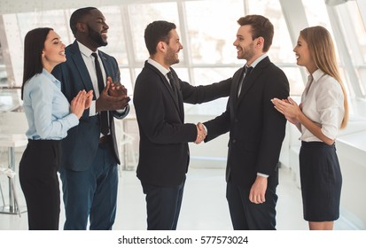 Beautiful business people in formal suits are smiling while two business partners are shaking hands in office