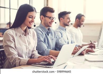 Pessoas de negócios bonitas em fones de ouvido estão usando computadores e sorrindo enquanto trabalham no escritório