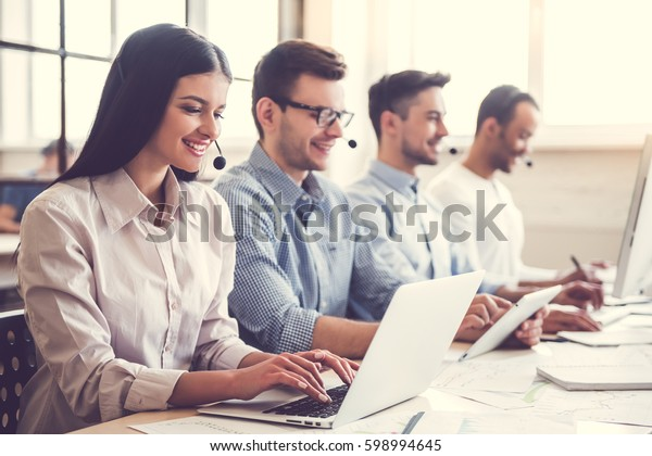 Beautiful business people in headsets are using computers and smiling while working in office