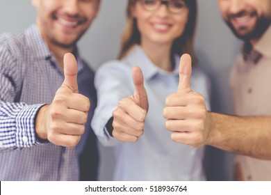 Beautiful business people are showing Ok signs, looking at camera and smiling, standing on gray background
