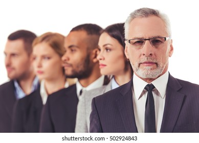 Beautiful business people in suits are standing one by one, handsome mature businessman in the foreground is looking at camera, isolated on a white