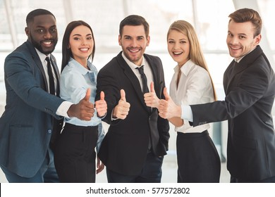 Beautiful business team in formal suits are looking at camera, showing thumbs and smiling while standing in office