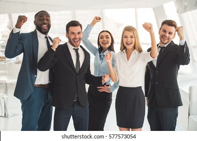 Beautiful business team in formal suits are raising hands in fists, looking at camera and smiling while standing in office