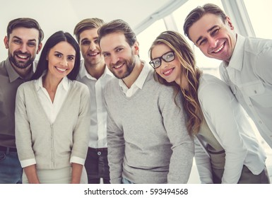 Beautiful business team is looking at camera and smiling while standing in office