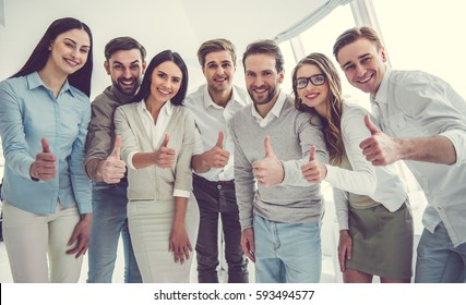 Beautiful business team is showing Ok sign, looking at camera and smiling while standing in office
