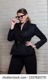 6f2680ec01 Beautiful business woman in black clothes and big horn-rimmed glasses.