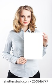 Beautiful business woman in a blue shirt isolated on white background. Beautiful blonde. white sheet. Girl holding a white sheet of paper