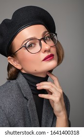 Beautiful business woman brunette in black beret and eyeglasses. Checking new eyeglasses