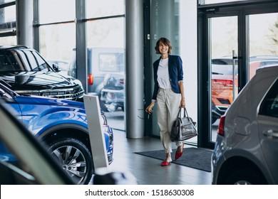 Beautiful business woman in a car showroom