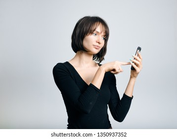 beautiful business woman clicks on the phone send, isolated on gray background