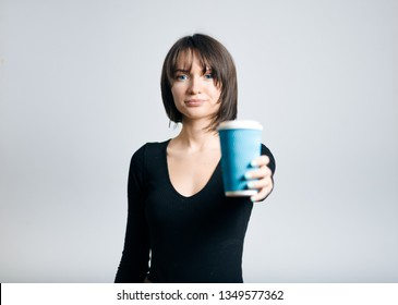 beautiful business woman with coffee to go, isolated on gray background