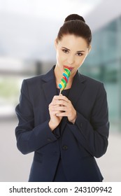 Beautiful business woman eating lollipop.