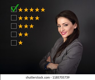 Beautiful business woman in grey suit looking happy with folded arms on dark grey background. The best rating, evaluation, online rewiew. Confident woman voting to five yellow star to increase