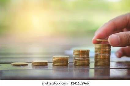 beautiful business woman hand but golden coins stack on wood table with blur nature bokeh background in park with sunrise financial bank saving concept ESG Environmental Social Governance startup.