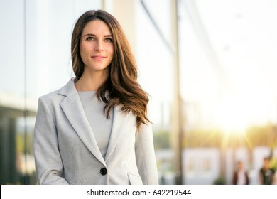 Beautiful business woman headshot lifestyle outdoor with sunlight flare a look of content