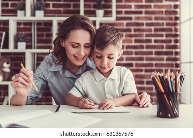 Beautiful business woman and her cute little son are drawing and smiling while sitting in office