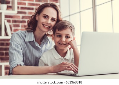 Beautiful business woman and her cute little son are using a laptop and smiling while sitting in office