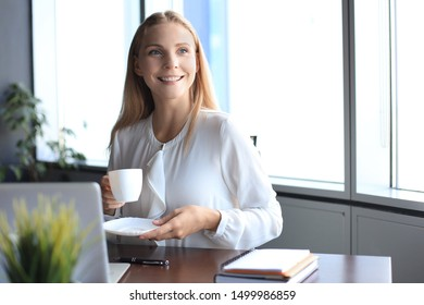 Beautiful business woman is holding coffee cup and smiling while sitting at her working place